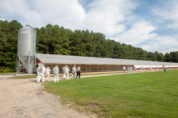 Image of poultry barn with people visiting dressed for biosecurity.  Image by Edwin Remsberg