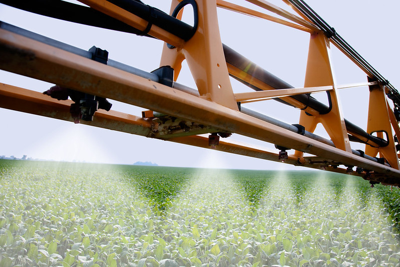 Image of sprayer boom spraying soybeans in the field