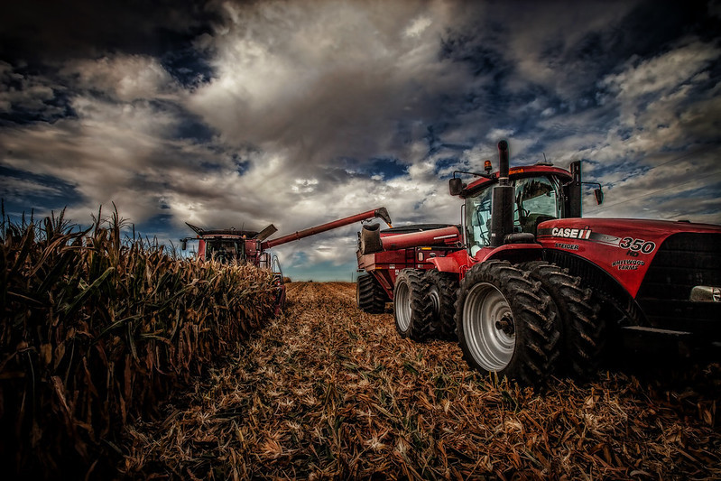 Corn harvest with combine dumping onto grain cart pulled by tractor. Image by Steven Baird via flickr.com