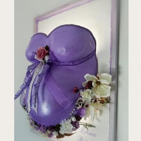 Romantischer Babybauchabdruck mit Blüten, an einem Rahmen und indirektem Licht