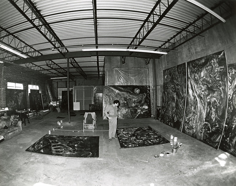 Kanso working in his Atlanta studio in the mid-1980s. A black and white photograph of Nabil Kanso in his expansive studio surrounded by large paintings on the walls and floor.