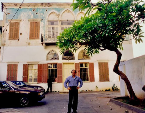 Nabil Kanso stands in front of his childhood home, a two-story structure, with cars and tree behind him; Beirut in 2007.