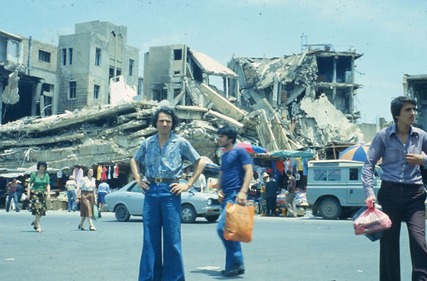 A color photo of Nabil Kanso standing in war torn Beirut (1978); with ruined buildings in the background, and people and motor vehicles passing by.