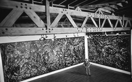 """Nabil Kanso stands arms akimbo in front of """"Warring Wings"""" (1984) and """"Naked Ghosts"""" (1985) at an exhibition in Atlanta at the Contemporary Art Center in 1985. A black and white photograph of the artist standing among two of his monumental paintings."""