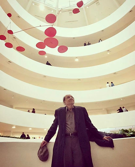 Nabil Kanso, in his 70s, enjoying the sunlit Guggenheim Museum atrium. with a red Alexander Calder mobile hanging behind him (2017).