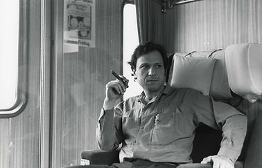 A black and white photo of Nabil Kanso seated in a train compartment smoking a cigar
