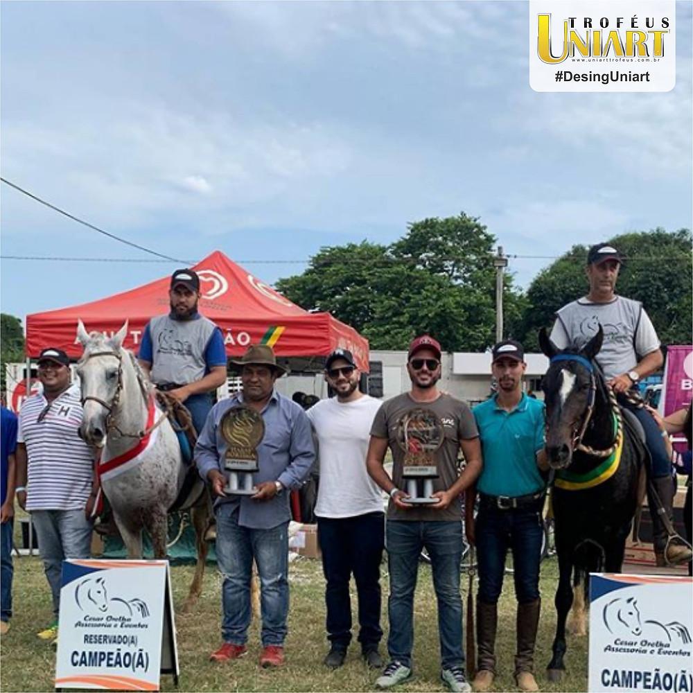 Premiação de Copa de Marcha, com adestradores montados nos cavalos que estão com escarapelas e homens ao lado segurando os troféus