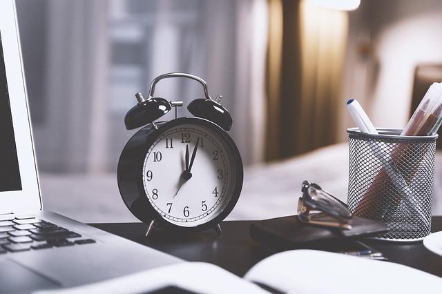 Mesa com relógio, notebook e porta-canetas sobre