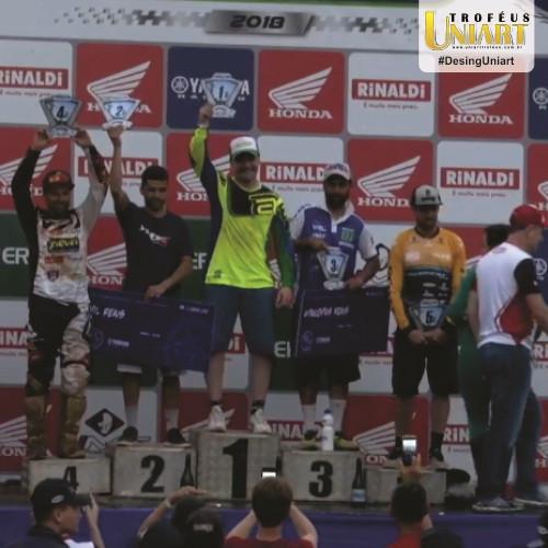 Vários motociclistas no pódio levantando seus troféus