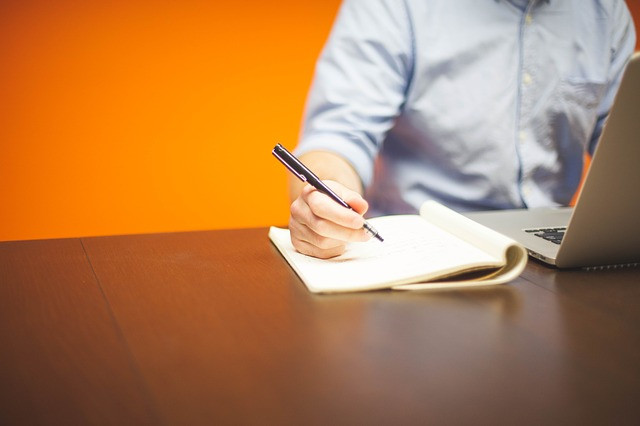 Homem mexendo em um notebook e anotando algo em um caderno