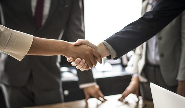 Pessoas apertando as mãos (fechando negócios) sobre a mesa