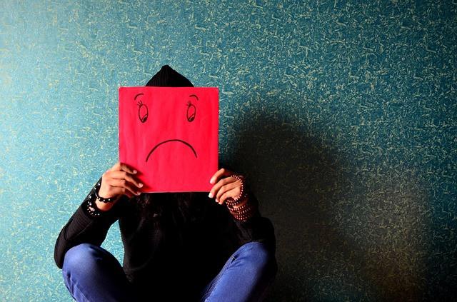 Pessoa sentada com folha na frente do rosto mostrando infelicidade