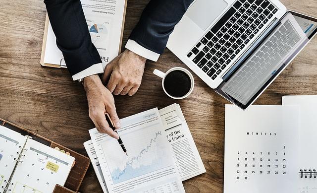 Homem mostrando gráficos com uma caneta sobre uma mesa com papéis, notebook e uma xícara de café