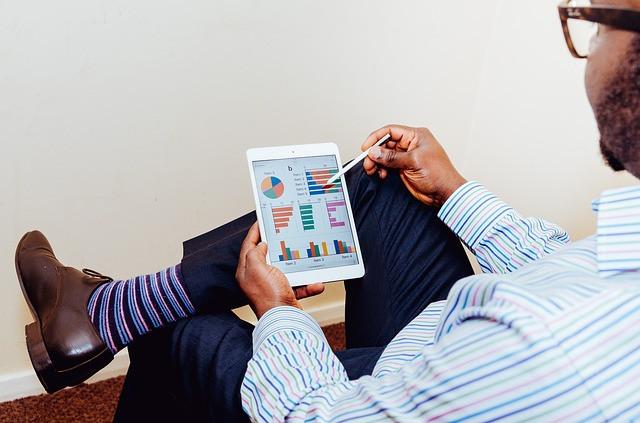 Homem sentado mexendo em um tablet que mostram gráficos