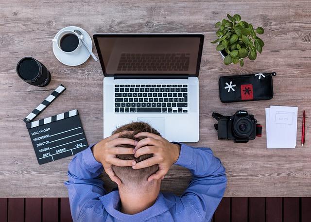 Homem com as mãos na cabeça sobre uma mesa com notebook, planta, café, claquete, câmera fotográfica, papel e caneta