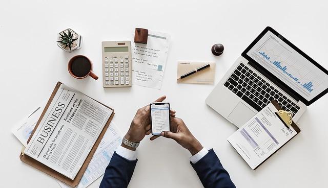 Pessoa mexendo no celular sobre a mesa com vários papéis, notebook, café e planta