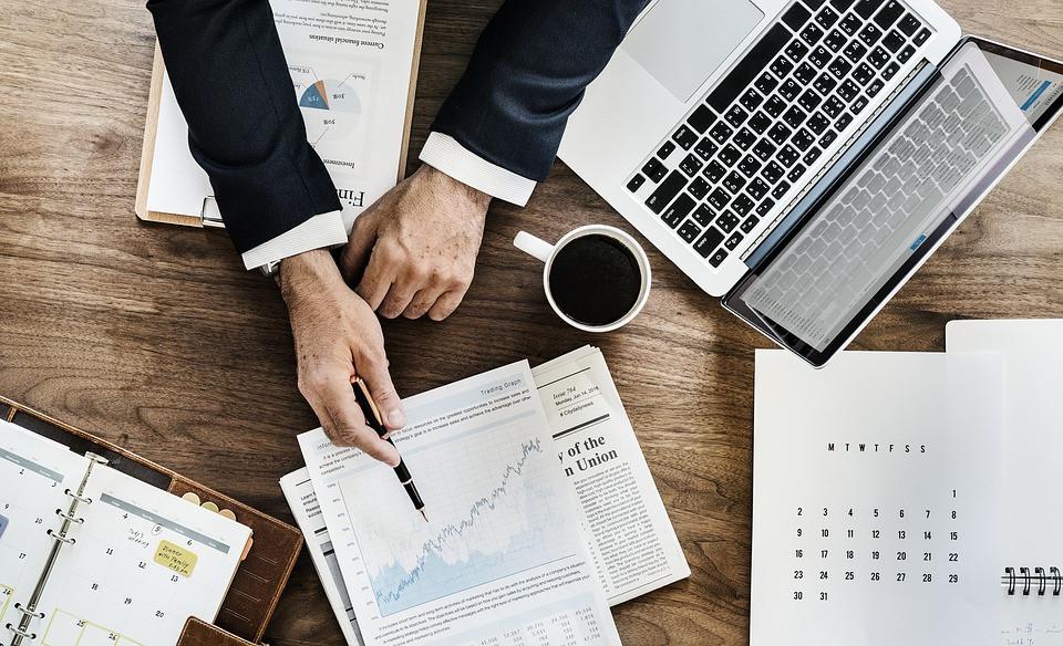 Homem apontando gráficos em um papel sobre uma mesa com xícara de café e notebook aberto ao lado