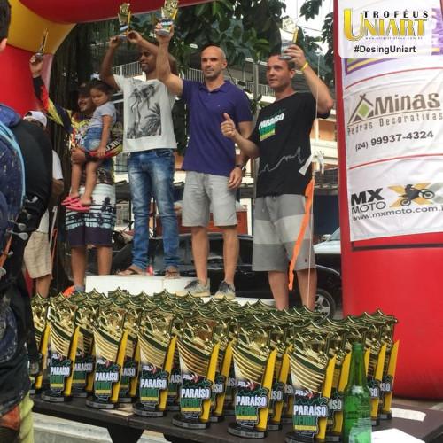 Três homens no pódio segurando troféu e à frente mesa com vários troféus do evento