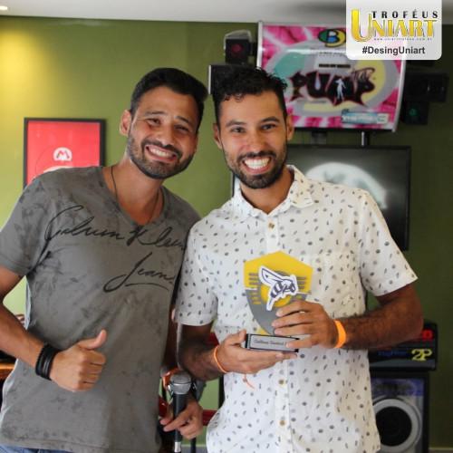 Dois homens na foto, um de camisa cinza e outro de camisa branca segurando troféu