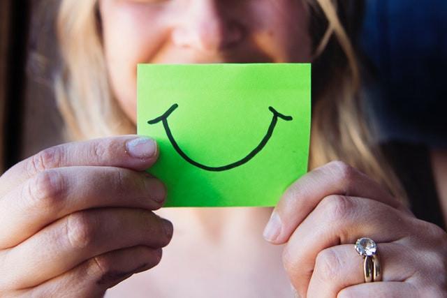Mulher segurando post-it com um sorriso desenhado