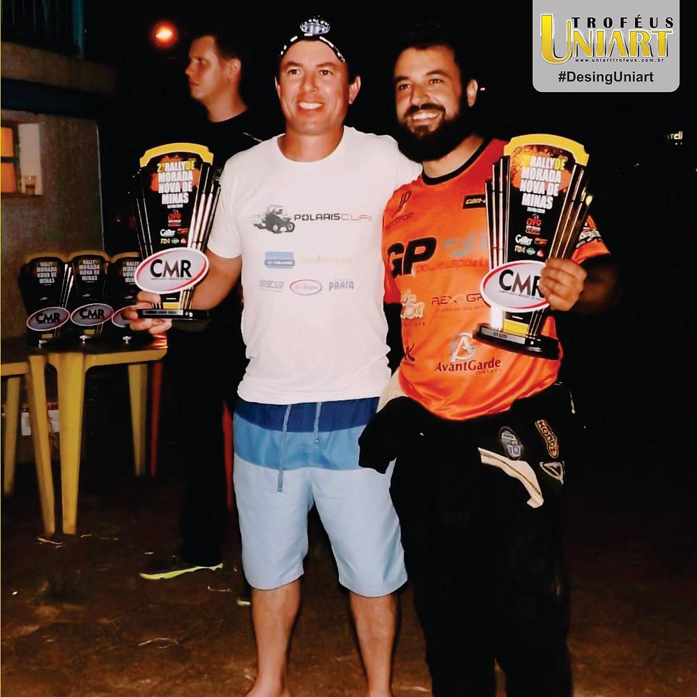 Homens segurando troféus de evento de rally