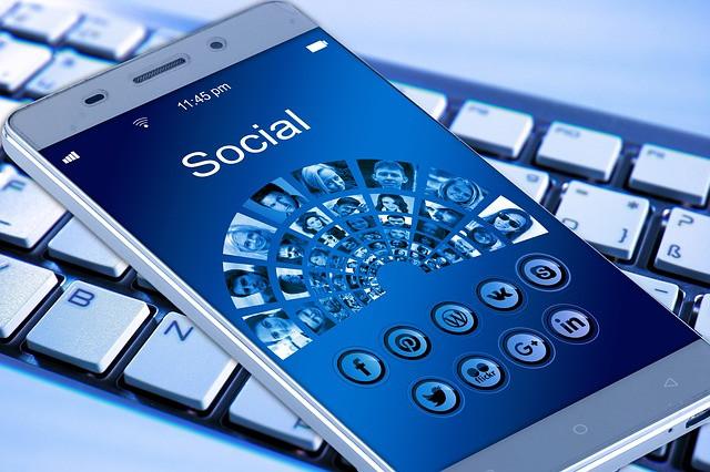 Celular sobre teclado de computador com tela mostrando várias redes sociais