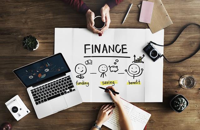 Pessoa escrevendo sobre finanças em um papel sobre uma mesa com câmera, notebook, planta, copo de água e outra pessoa segurando uma xícara de café