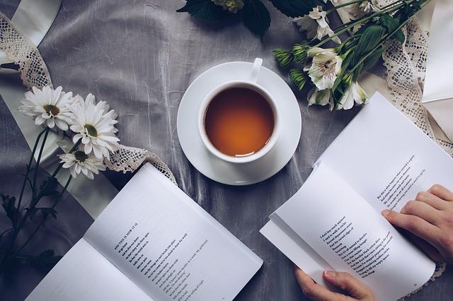 Pessoa lendo um livro, com chá a sua frente e flores