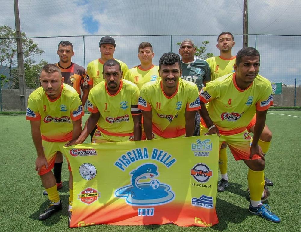 Equipe masculina de futebol com uniforme amarelo e bandeira do time Piscina Bella