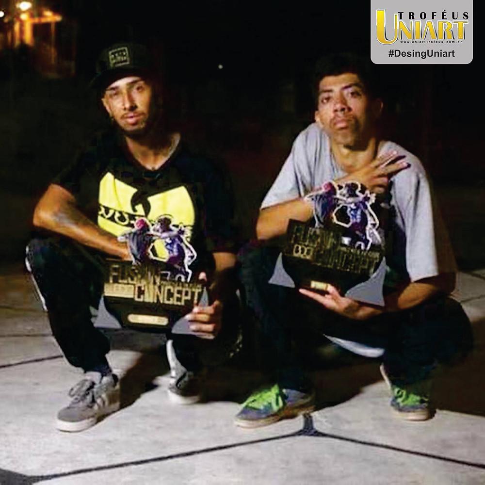 Dois homens agachados segurando troféus de MDF com aplicação de acrílico espelho ouro