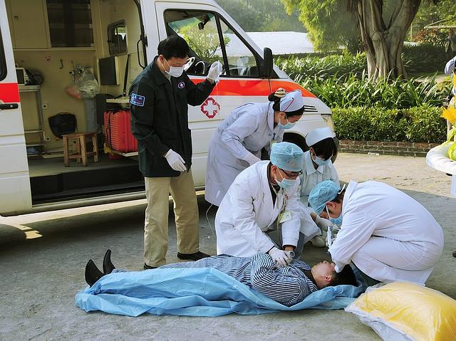 Ambulância parada com médicos e socorristas prestando socorros