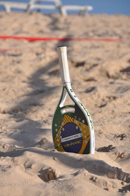 Raquete com desenho da bandeira do Brasil na areia da praia