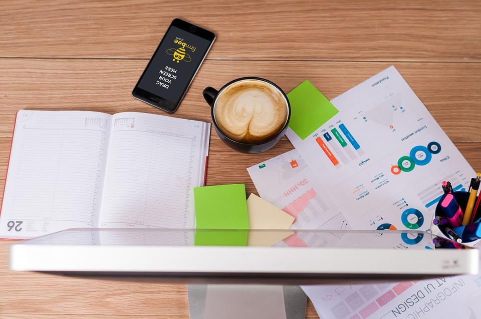 Tela de computador, papéis, celular e xícara de café sobre a mesa