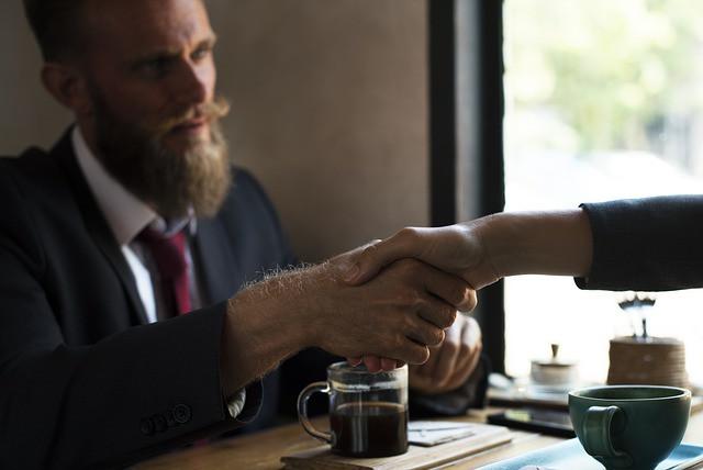 Duas pessoas dando um aperto de mãos