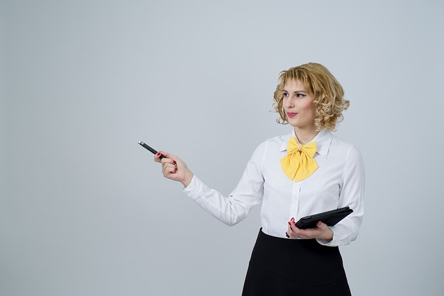 Mulher com tablet em mãos e apontando com uma caneta