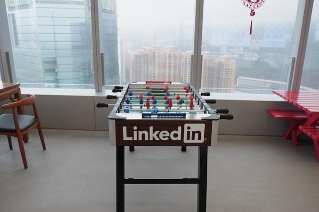 Mesa de pebolim com logo do LinkedIn em meio a uma sala de lazer