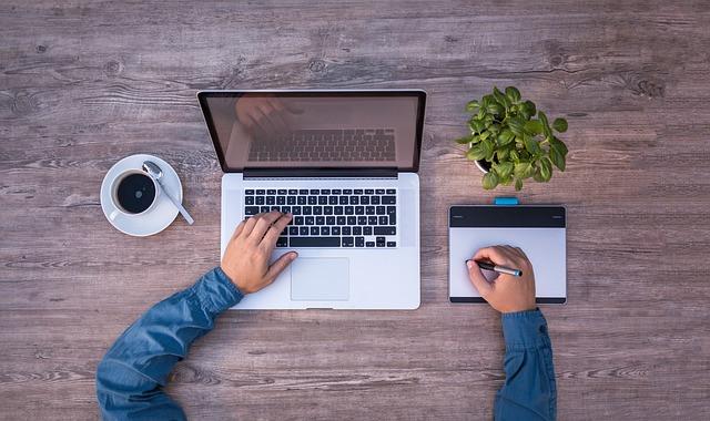 Pessoa mexendo em computador com planta e xícara de café ao seu lado