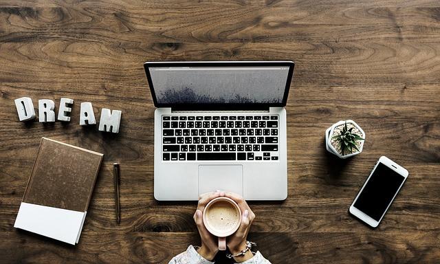 Pessoa segurando xícara de café sobre mesa com celular, notebook, planta, agenda e caneta