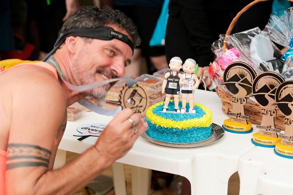 Marco Antonio segurando uma medalha do Treinão ao lado de um bolo com bonecos dele e da esposa