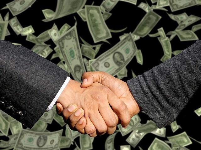 Aperto de mãos em frente ao fundo de dólares