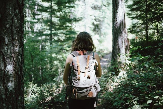 Mulher com mochila de trekking nas costas em meio à floresta