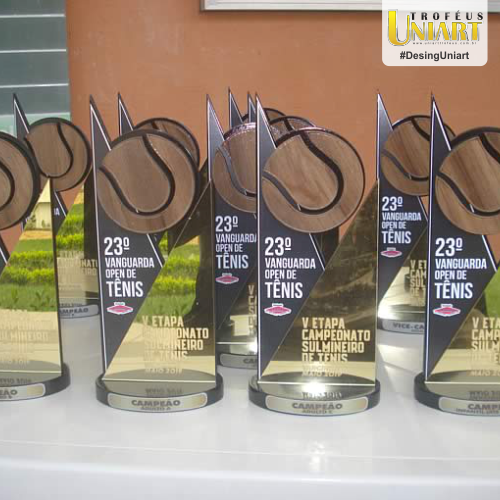 Vários troféus de MDF, com bola de tênis em MDF encapado e acrílico gravado com nome do evento sobre a mesa