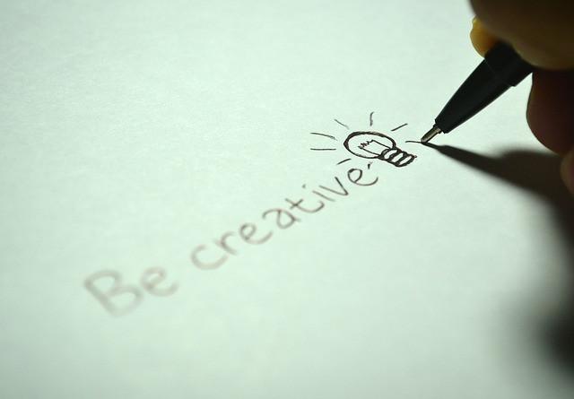 """Pessoa escrevendo """"Be creative"""" em um papel"""