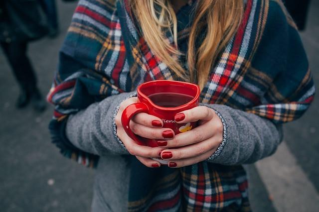 Mulher com vários casacos e segurando xícara