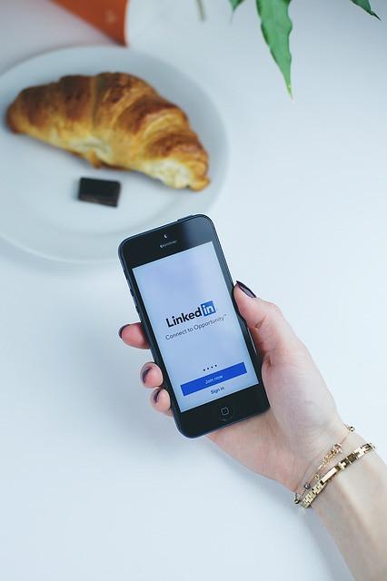 Mulher com smartphone nas mãos com LinkedIn aberto e croissant ao fundo