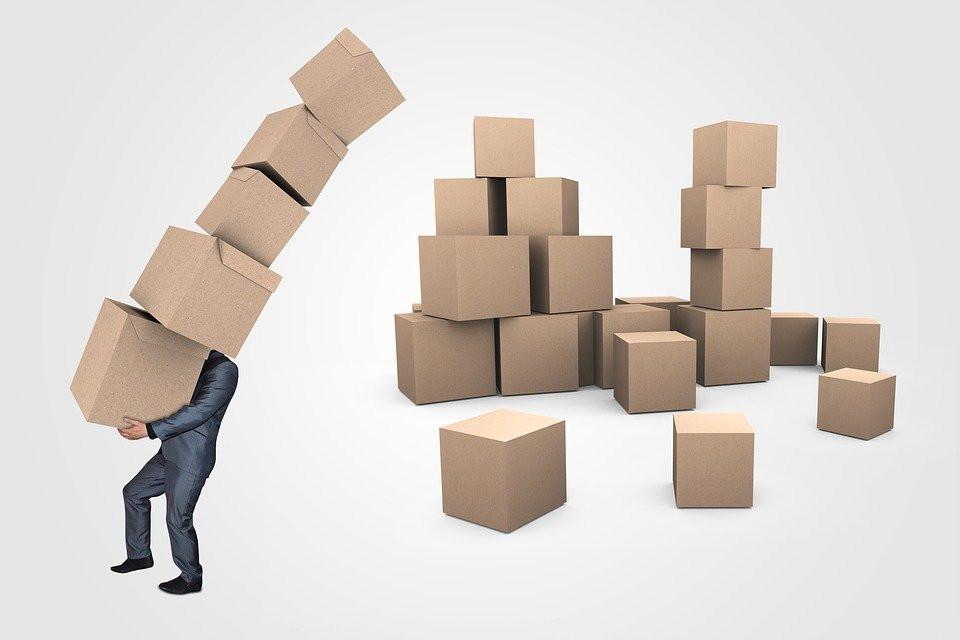 Homem carregando várias caixas e outras caixas no chão ainda