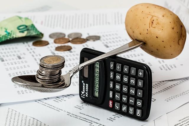 Colher equilibrando sobre calculadora uma batata e moedas e ao fundo papéis, notas e moedas