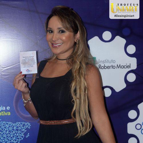 Mulher com vestido preto em premiação com placa de acrílico