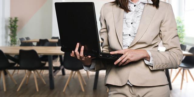 Mulher com notebook nas mãos em sala de reunião