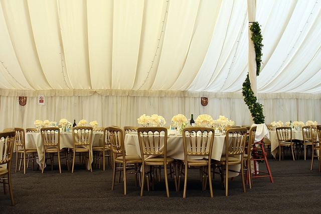 Salão ornamentado para um coquetel com mesas e cadeiras organizadas